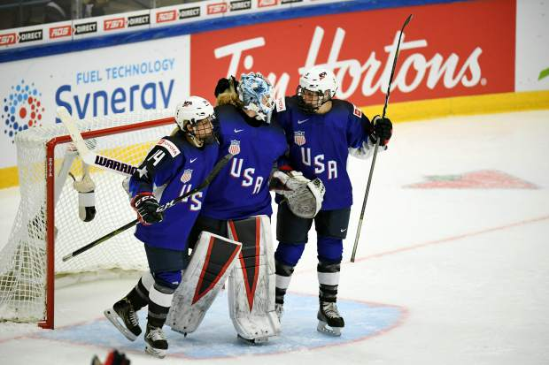 Brianna Decker, left, Alex Rigsby and Cayla Barnes of Team USA celebrate winning the 2019 IIHF Women's World Championships preliminary match between the USA and Canada in Espoo, Finland on Saturday.