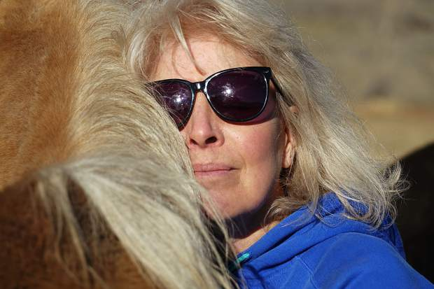 "Volunteer Karen Johns gives a horse some love at the Blue River Horse Center about 20 miles north of Silverthorne. As the center gets ready for another summer season, Johns said the work she sees there is ""truly magical."""