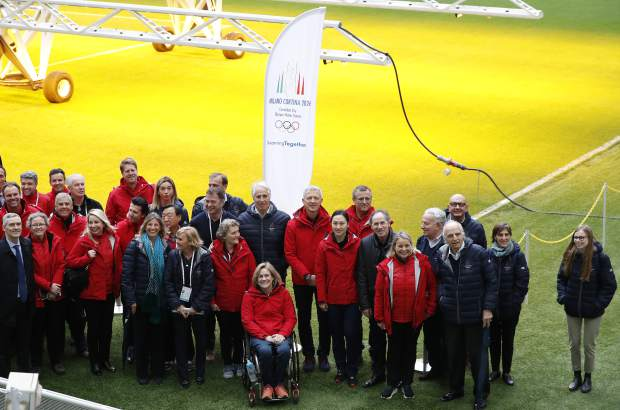 Members of the Winter Olympics Milano Cortina bid IOC Evaluation Commission pose on the grass of San Siro stadium, in Milan, Italy on Thursday.