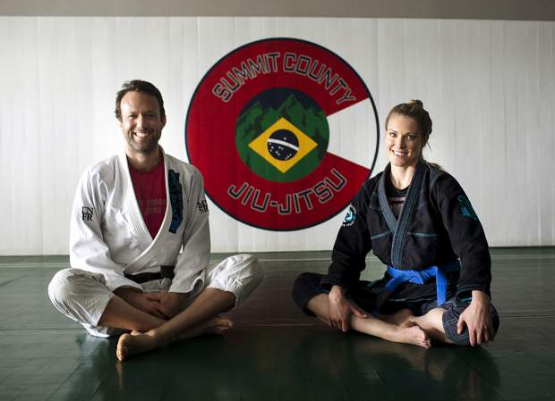 Summit County Jiu Jitsu owner Douglas Cuomo (left) and gym member Asti Alexandria pose for a photograph on the mat at Summit County Jiu Jitsu on Wednesday, April 10, at the martial arts gym in Frisco.