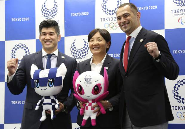 From left, Men's Judo Japan national team head coach Kosei Inoue, Women's Softball Japan national team head coach Reika Utsugi and Tokyo 2020 Sports Director Koji Murofushi pose for a photo after a press conference to unveil detailed Olympic competition schedule in Tokyo on Tuesday. For fans, athletes, and volunteers in Japan, next year's Olympics in Tokyo could become known as the get-up-early games.