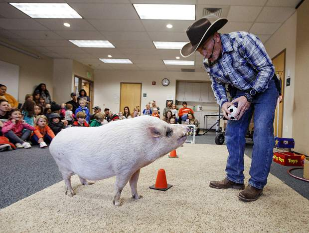 Mudslinger receives instructions to move the soccer ball to a goal during a performance led by Top Hogs' John Vincent, right, Thursday, April 18, at the Summit County Library in Frisco.