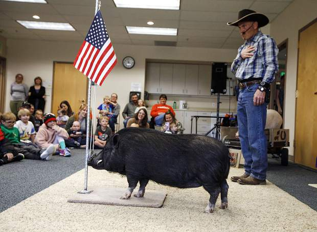 Digger, a pig, raises the flag during a performance led by Top Hogs' John Vincent, right, Thursday, April 18, at the Summit County Library in Frisco.