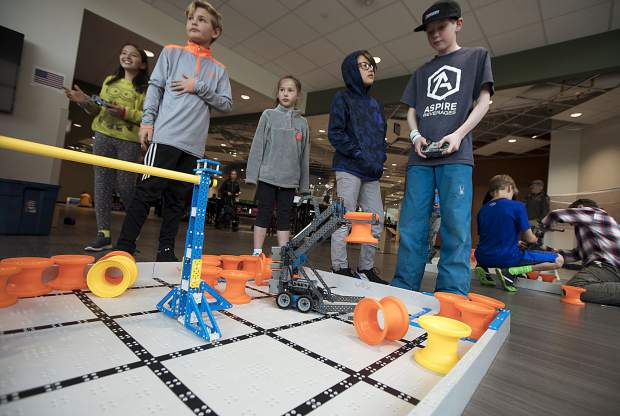 Local students navigate the remote controlled robots with placing the orange hubs Wednesday, April 3, inside the school in Frisco.