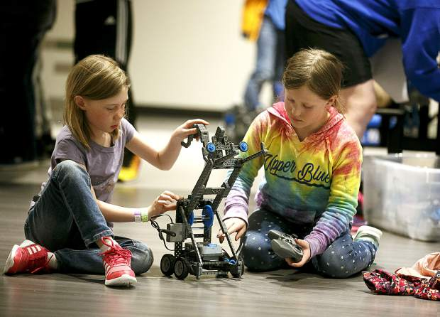 Local third-graders Zoe Gauss, left, and Luella Krawczuk-Cochrane tests the remote controlled robot Wednesday, April 3, inside the school in Frisco.