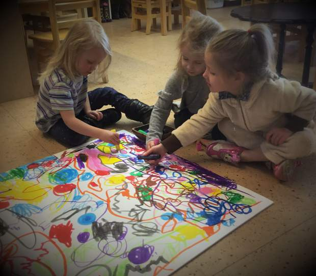 4-year-olds Britta Peterson, Nora Heavern and Monica Ness Monteverde work on a piece of art together. Community is the theme of Timberline Learning Center's art show this year.