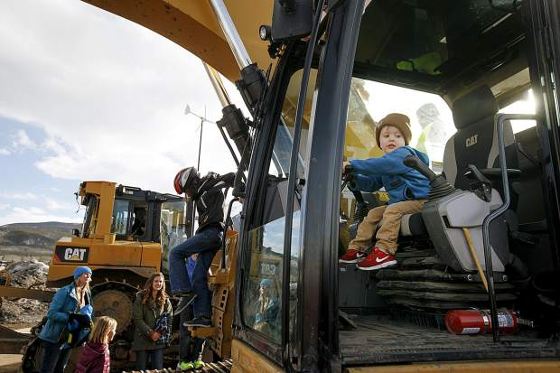 Local children explore the heavy machinery equipment during the
