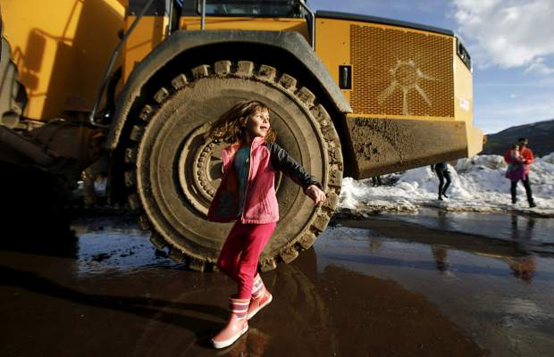 A young girl runs around the heavy machinery equipment during the