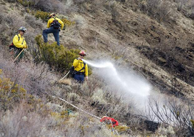 Wildland firefighters work to contain a brushfire between Blue River Valley Ranch and Angler Mountain Ranch Saturday, April 20, in Silverthorne. The fire was the first wildfire in Summit County in 2019, and was sparked by an authorized slash pile burn that got out of control.