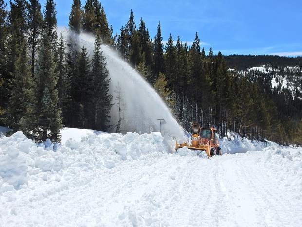 A CDOT grader fitted with a snowblower shoots snow into the air while clearing Highway 82 on Independence Pass on Thursday.