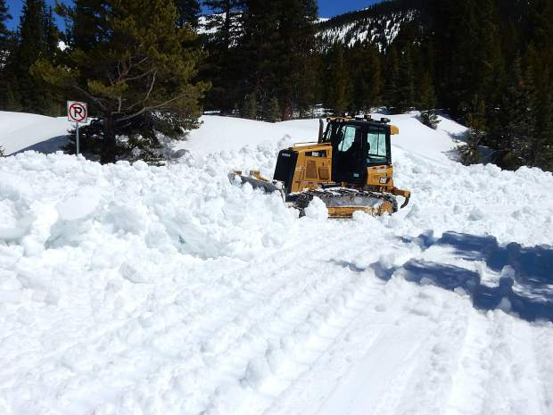 A small bulldozer plows snow from the hairpin turn above lower Lost Man on Thursday.