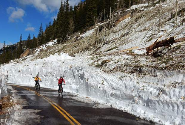 Karin Teague of the Independence Pass Foundation and Greg Albrecht ride their mountain bikes through the Green Mountain avalanche debris on Highway 82 east of Aspen on Thursday. They're carrying their skis for the climb where the road isn't plowed.