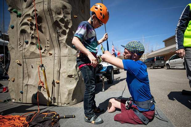 Medic veteran Feet Jensen adjusts his son, James', 11, harness at the rock climbing wall outside of the Westin in Snowmass on April 1 for the National Disabled Veterans winter sports clinic.