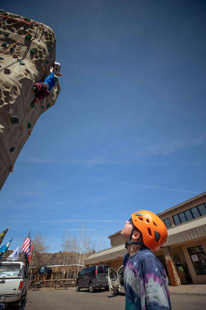 Medic veteran Feet Jensen on the rock climbing wall outside of the Westin in Snowmass on April 1 for the National Disabled Veterans winter sports clinic. His son, James, 11, cheers him on below.