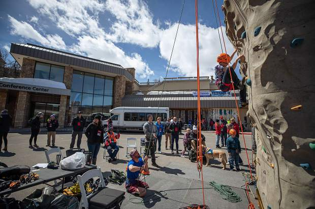 Medic veteran Feet Jensen belays his son, James, 11, on the rock climbing wall outside of the Westin in Snowmass on April 1 for the National Disabled Veterans winter sports clinic.