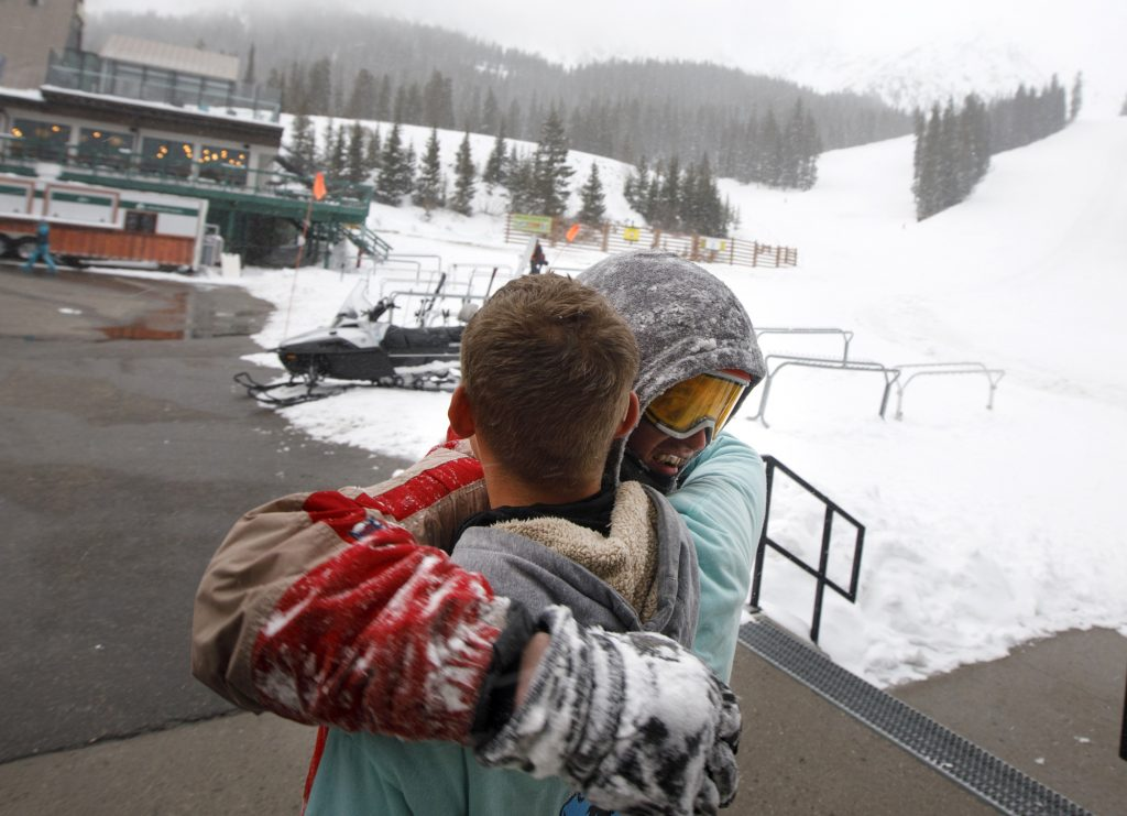 Snowboarders John Moser, in back, hugs his friend Patrick Powers after being rescued from out-of-bounds following an avalanche incident Tuesday evening, May 21, at Arapahoe Basin Ski Area. Moser, who was found by Summit County Rescue Group, was swept by an avalanche as he and Powers were attempting to hike back inbounds.