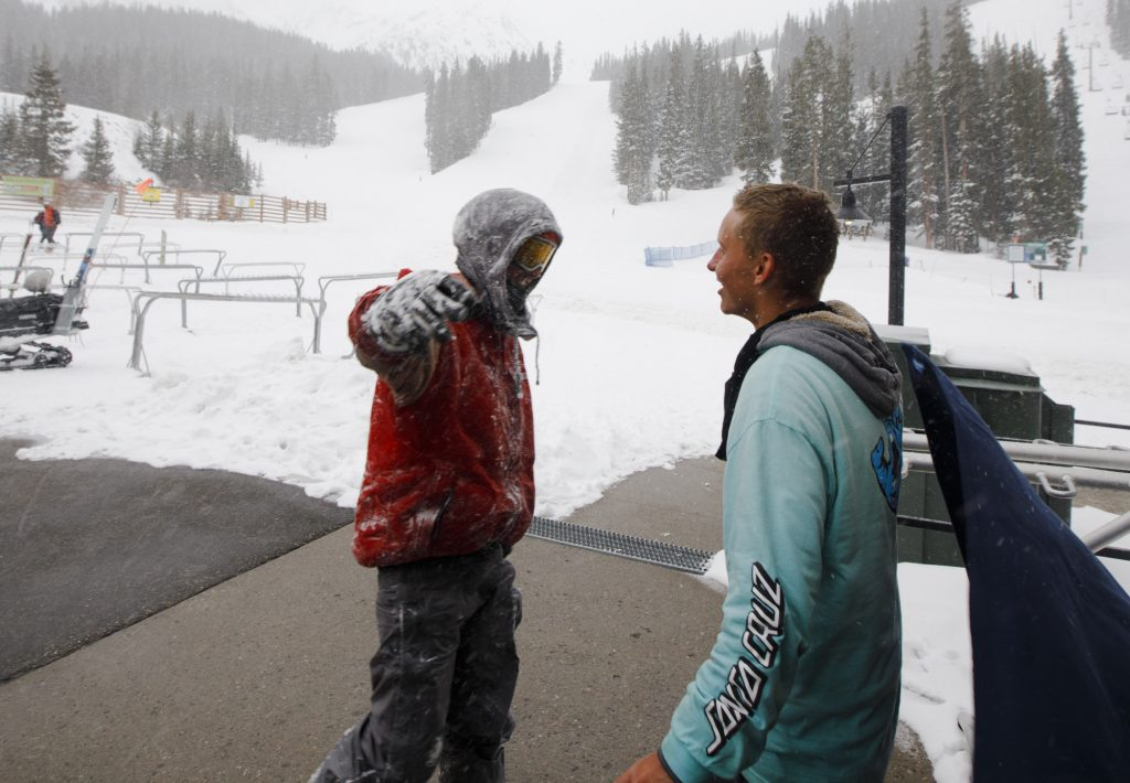Snowboarders John Moser, left, reach out to hug his friend Patrick Powers after being rescued from out-of-bounds following an avalanche incident Tuesday evening, May 21, at Arapahoe Basin Ski Area. Moser, who was found by Summit County Rescue Group, was swept by an avalanche as he and Powers were attempting to hike back inbounds.