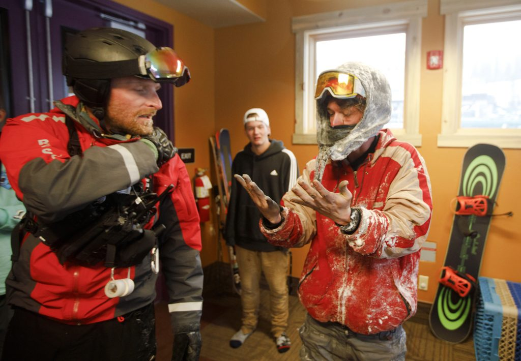 Snowboarder John Moser looks at his hands next to Summit County Rescue Group member Devon Haire after being rescued from out-of-bounds following an avalanche incident Tuesday evening, May 21, at Arapahoe Basin Ski Area. Moser, who was found by Summit County Rescue Group, was swept by an avalanche as he and his friend Patrick Powers were attempting to hike back inbounds.