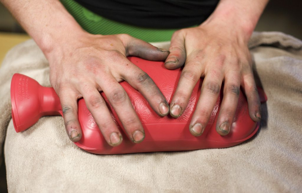 Snowboarder John Moser warms his fingers, covered in dirt from his gloves, on a rubber hot water bottle after being rescued Tuesday evening, May 21, at Arapahoe Basin Ski Area. Moser, who was found by Summit County Rescue Group, was swept by an avalanche as he and Powers were attempting to hike back inbounds.