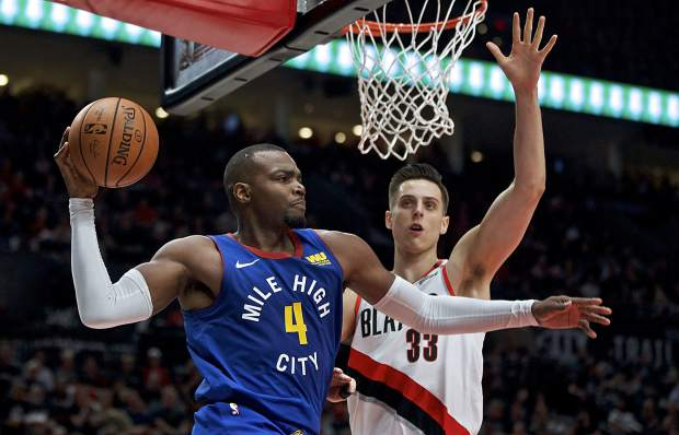 Denver Nuggets forward Paul Millsap, left, looks to pass the ball around Portland Trail Blazers forward Zach Collins during the first half of Game 6 of an NBA basketball second-round playoff series on Thursday in Portland, Oregon.