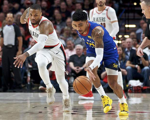 Denver Nuggets guard Gary Harris, right, gathers a loose ball in front of Portland Trail Blazers guard Damian Lillard during the first half of Game 3 of an NBA basketball second-round playoff series on May 3 in Portland, Oregon.