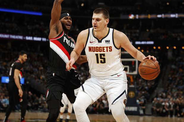 Denver Nuggets center Nikola Jokic, right, drives to the rim for a basket as Portland Trail Blazers forward Maurice Harkless defends in the first half of Game 5 of an NBA basketball second-round playoff series on Tuesday in Denver.