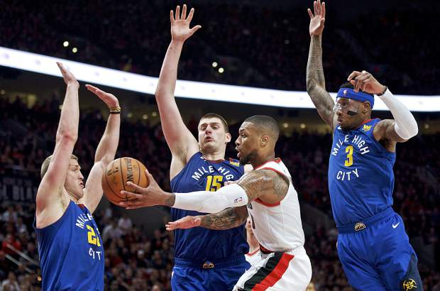 Portland Trail Blazers guard Damian Lillard, center, passes the ball away from Denver Nuggets forward Mason Plumlee, left, center Nikola Jokic, second from left, and forward Torrey Craig, right, during overtime of Game 3 of an NBA basketball second-round playoff series on May 3 in Portland, Oregon.