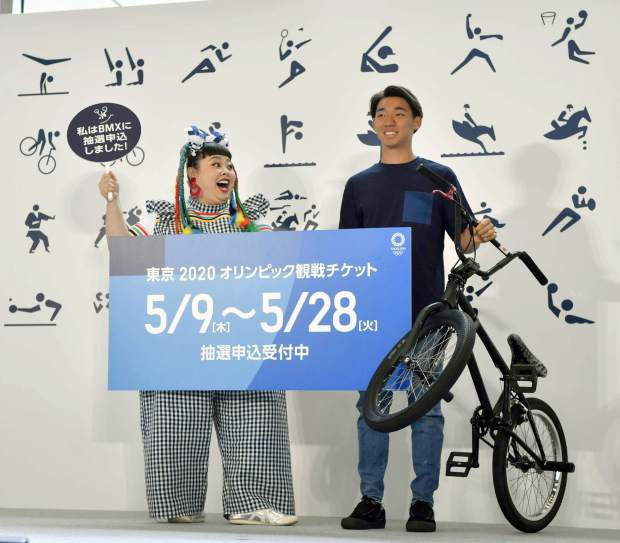 Japanese comedian Naomi Watanabe, left, and BMX rider Rimu Nakamura attend an event to mark the start of application to buy tickets for the 2020 Tokyo Olympic Games, in Tokyo on Thursday, May 8. Japan residents began Thursday entering a lottery system, hoping to land tickets for next year's Tokyo Olympics. The sign reads