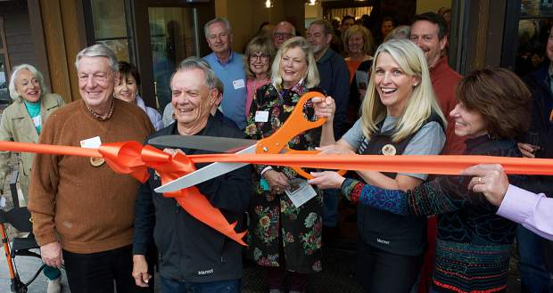 """In front, Doug Sims, left, Howard Carver, center, and Ellen Reid, with scissors, celebrate the grand opening of a new 5,900-square-foot building, called """"Tieken Place,"""" on Thursday at Keystone Science School. Reid is the school's executive director while Sims and Carver have deep ties to the school and were instrumental to the capital campaign that raised $3.95 million for the project. The trio is flanked by dozens of donors and supporters of the school."""
