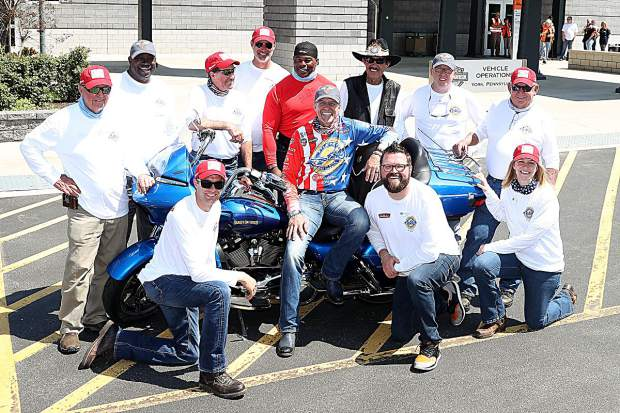 Over 25 years, Kyle Petty's (seated center) charitable Ride Across America has featured other NASCAR and sports stars. This year, such stars as Petty's father Richard Petty (back row, third from right) and football legend Herschel Walker (back row fourth from right) will again join the ride, which will pit-stop in Buena Vista on Monday at 10:30 a.m.