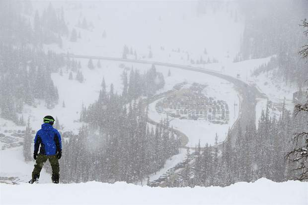 A snowboarder eyes the descent on the front-side of Arapahoe Basin Ski Area Tuesday morning in the midst of a May spring snow storm that dropped more than 6 inches of powder overnight Monday evening into Tuesday morning at the Summit County ski area at the Continental Divide, with snow continuing to descend throughout the day.