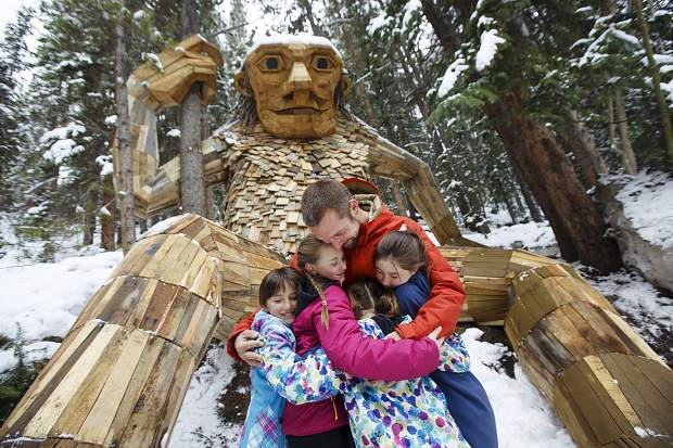 Artist Thomas Dambo, of Denmark, hugs local girls and heartstone founders Tori Garner, Lexi Garner, Jade Batdorff and Paige Batdorff in front of his troll sculpture Isak Heartstone. Friday, May 10 at the trolls new home in Breckenridge.