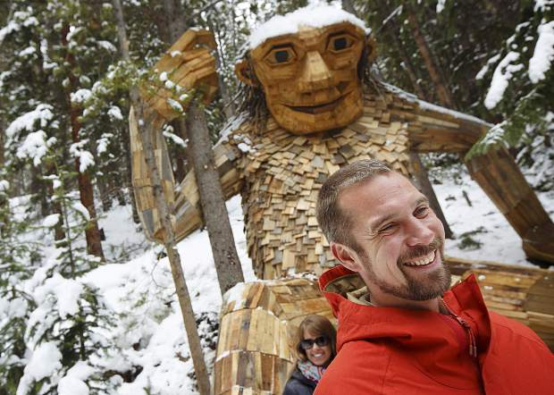 Thomas Dambo, of Denmark, smiles in front of his troll sculpture creation Isak Heartstone, Friday, May 10, in Breckenridge.