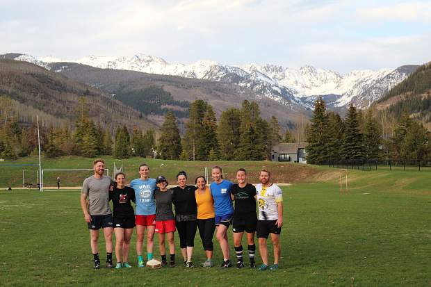 The Vail Women's Rugby team practices with the men's Vail Rugby team at Ford Park in Vail, with views of the Gore Range.
