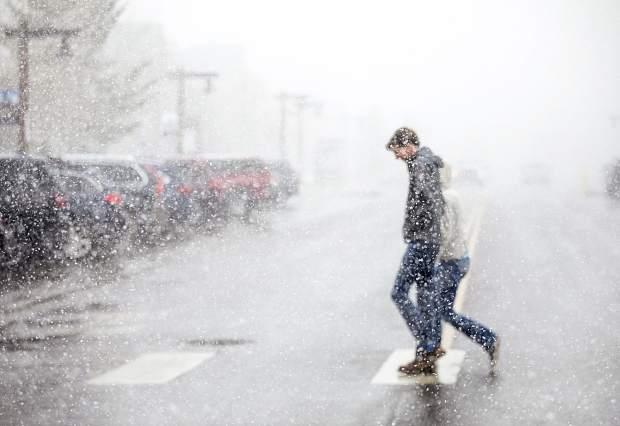 Pedestrians cross Main Street in Frisco as snowfall arrives Tuesday, April 2018. Spring continues to dump moisture in the mountains, with another week of snow and rain predicted.