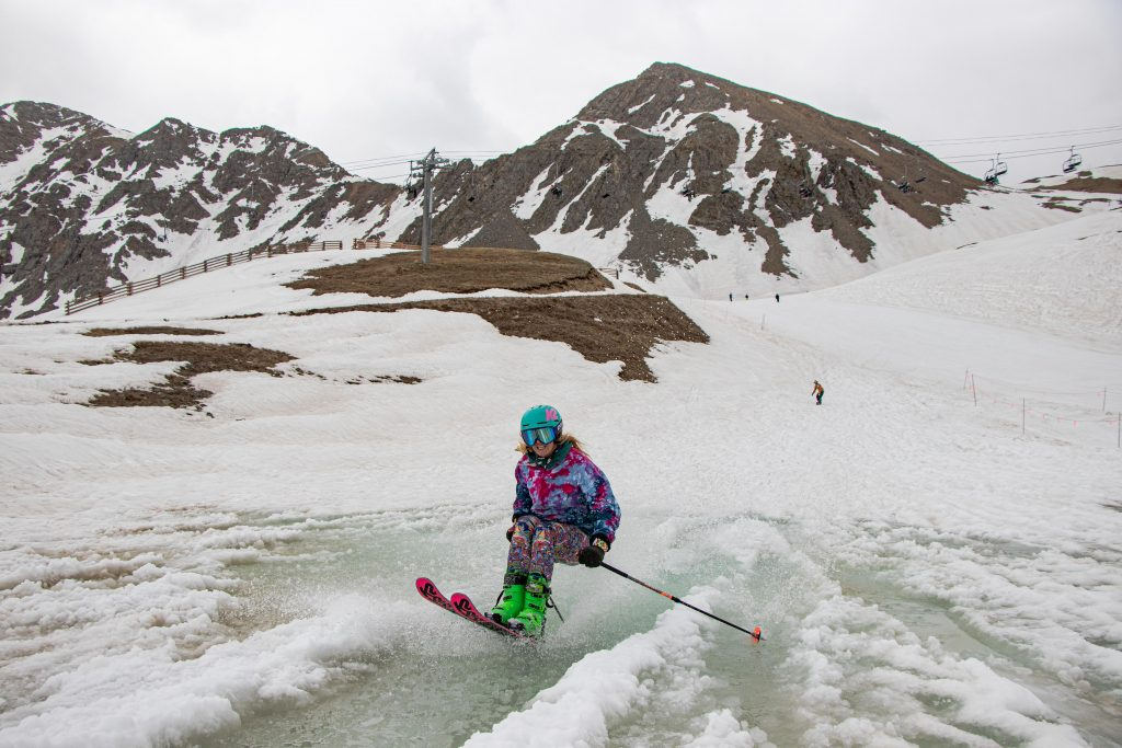 A skier transitions from the slushy on-mountain snow to the waters of Lake Reveal while skiing at Arapahoe Basin Ski Area last weekend.