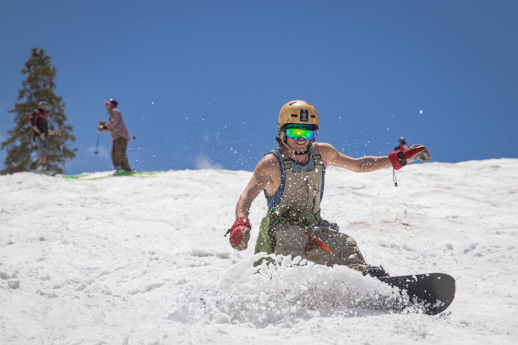 A snowboarder kicks-up slushy, spring — err, summer — snow while riding at Arapahoe Basin Ski Area in late June