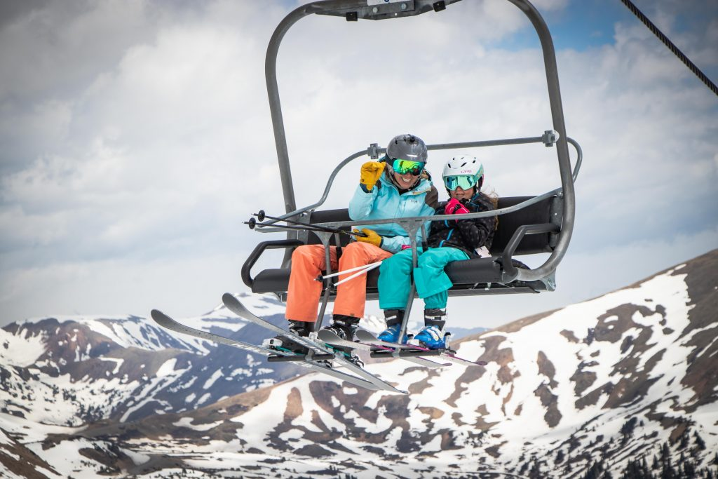 Skiers ride a chairlift up while summer skiing at Arapahoe Basin Ski Area in June 2019.