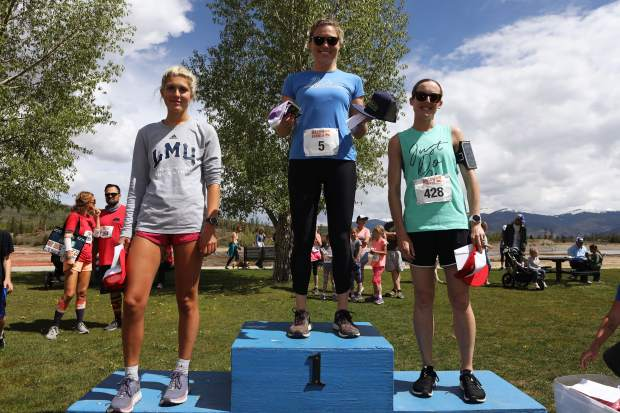 Race winner Steph Anderson (center) stands atop the podium along with runner-up Jenny Wong (right) and third-place finisher Emily Sandberg after the trio finished at the top of Saturday's Bacon Burner 6K women's race in Frisco.