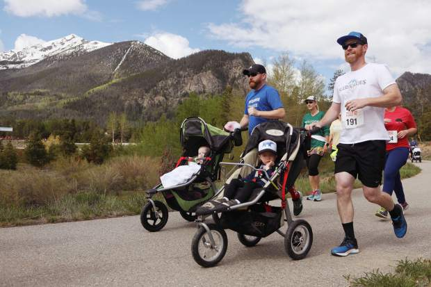 Patrick Jacox pushes a stroller while taking part in Saturday's Bacon Burner 6K race in Frisco, Mount Royal, Victoria Peak and Peak 1 in view at rear. Jacox finished in fifth-place in the 132-participant Walk Family competition.