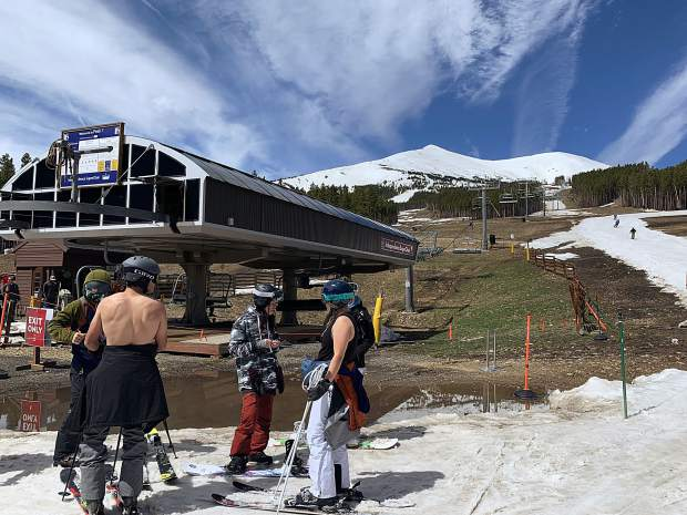 A shirtless skier chats with friends before loading the Independence SuperChair at Breckenridge Ski Resort during the resort's closing day for the extended 2018-19 winter season on Sunday. At rear, you can see the skiing and riding trail Breckenridge concocted atop mud-season conditions from the remaining snow at the base of Peak 7 to keep winter operations going through Sunday.