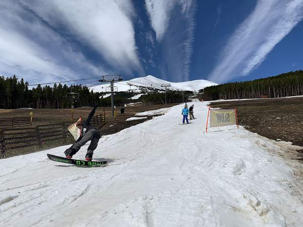 A snowboarder butters over some spring slush at the base of the groomed skiing and riding run Breckenridge Ski Resort constructed leading into the Peak 7 Independence SuperChair during Sunday's closing day of the extended 2018-19 winter season. At rear, the top of the resort's Peak 8 terrain is in view, terrain that was available for skiing and riding from the top of the Imperial Express SuperChair on Sunday. Breckenridge will begin operating its BreckConnect Gondola from downtown to the base of Peak 8 on Friday, the start of the resort's summer operations -- just five days after the resort closed for