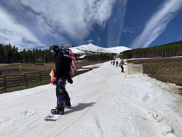 A snowboarder rides with an American flag at his back at the base of the groomed skiing and riding run Breckenridge Ski Resort constructed leading into the Peak 7 Independence SuperChair during Sunday's closing day of the extended 2018-19 winter season. At rear, the top of the resort's Peak 8 terrain is in view, terrain that was available for skiing and riding from the top of the Imperial Express SuperChair on Sunday. Breckenridge will begin operating its BreckConnect Gondola from downtown to the base of Peak 8 on Friday, the start of the resort's summer operations -- just five days after the resort closed for