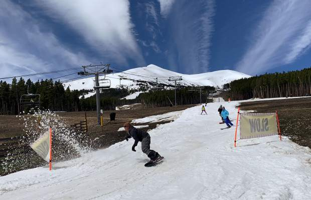 A snowboarder kicks up some spring slush at the base of the groomed skiing and riding run Breckenridge Ski Resort constructed leading into the Peak 7 Independence SuperChair during Sunday's closing day of the extended 2018-19 winter season. At rear, the top of the resort's Peak 8 terrain is in view, terrain that was available for skiing and riding from the top of the Imperial Express SuperChair on Sunday. Breckenridge will begin operating its BreckConnect Gondola from downtown to the base of Peak 8 on Friday, the start of the resort's summer operations -- just five days after the resort closed for