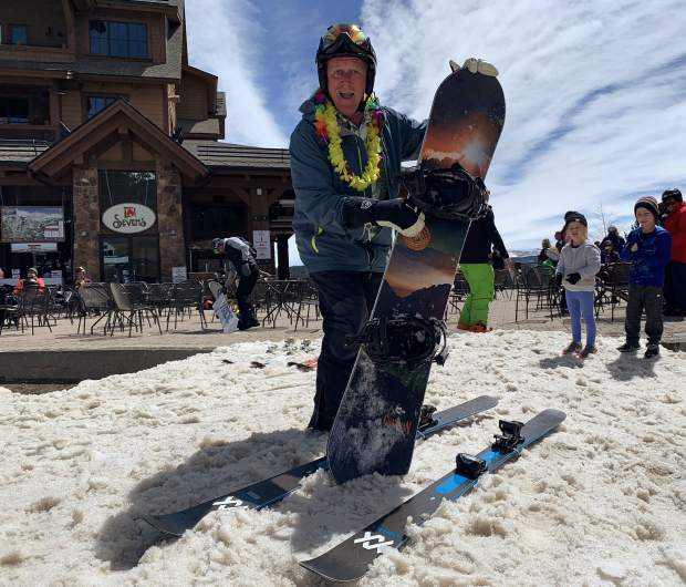 A snowboarder stakes his claim to what appears to be skier's territory while kids playing with snowballs in the background look on at the base of the Independence SuperChair on Peak 7 at Breckenridge Ski Resort during the resort's closing day for the extended 2018-19 winter season. Breckenridge will begin operating its BreckConnect Gondola from downtown to the base of Peak 8 on Friday, the start of the resort's summer operations -- just five days after the resort closed for