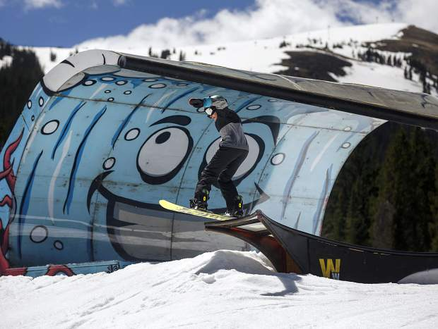 A young snowboarder launches off of a summer-themed rail next to a giant-wave feature at Woodward Copper's Pipeline Park on Wednesday, June 12, at Copper Mountain Resort.
