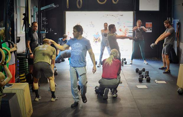 The owner of CrossFit Breckenridge, Dan Messinger, walks through the gym as people go through a workout he created in honor of the gym's founder and his fiend, David Scott Ferguson, during a June 1 fundraiser for a scholarship in Ferguson's name.