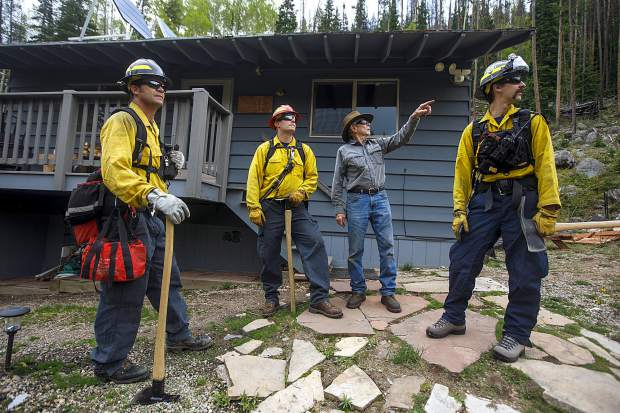 Summit Fire and EMS wildland firefighters Rob Beesley, far left, Doug Beeler, and Conrad Scoville chat with local resident Gary Grady about potential fire dangers Thursday June 20, along Boulder Creek near Silverthorne.