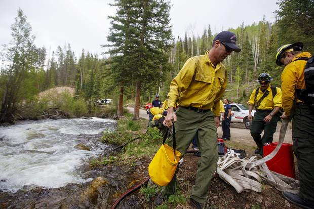 Summit Fire and EMS wildland firefighters take advantage of Boulder Creek as water source to protect homes from wildfires during a training scenario Thursday June 20, near Silverthorne.