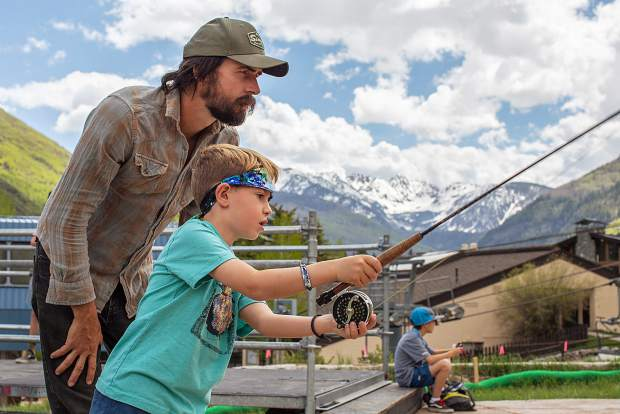 Robby Capps, of Pig Farm Ink., shows Holden Mitchell, from Los Angeles, how to cast a fly-fishing rod Friday at the GoPro Mountain Games. Capps helped determine the winner of the Fly Tying Competition on Friday.